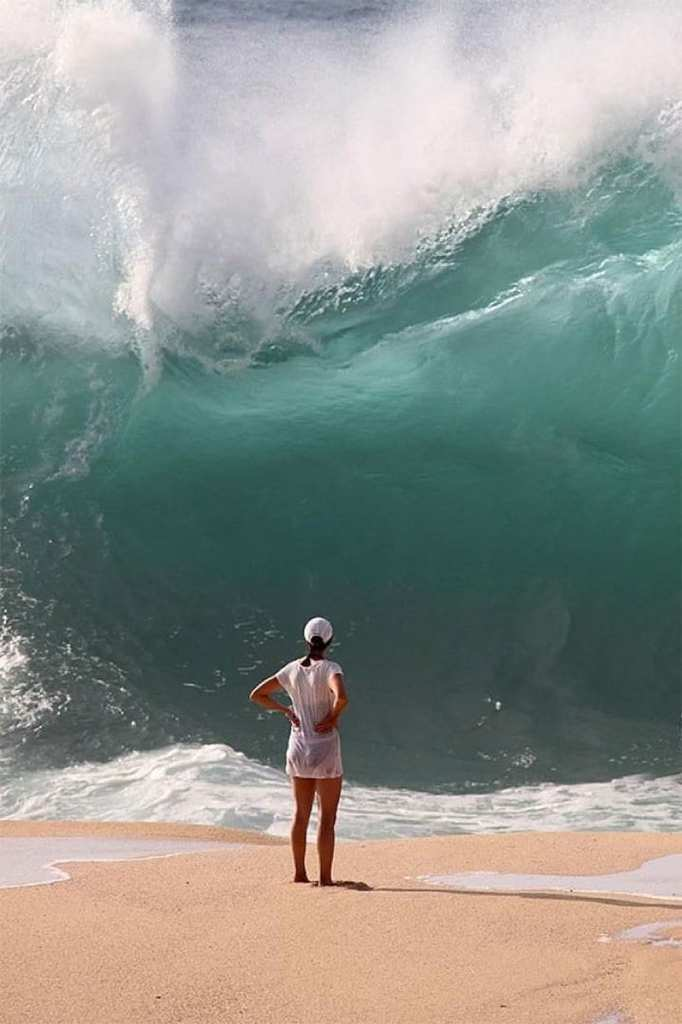 Girl standing in front of a large wave